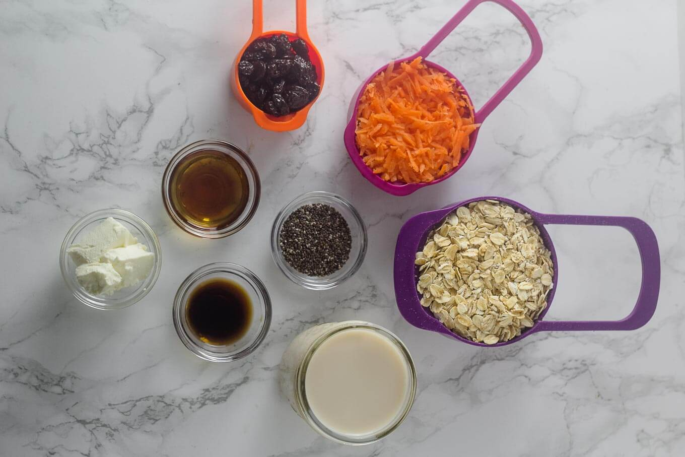 measuring cups with ingredients (oats, carrots, raisins, maple syrup, chia seeds, milk, vanilla extract) in them.