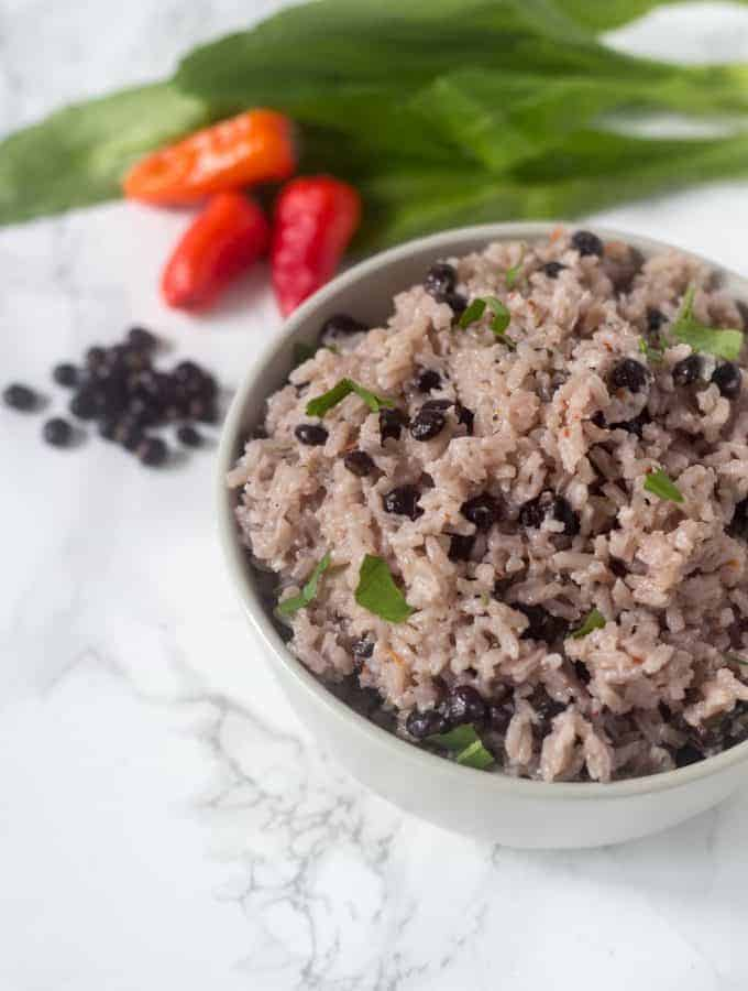 a bowl served that has rice with pigeon peas and coconut